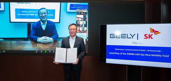 SK Holdings CEO Jang Dong-hyun, right, and Zhejiang Geely Holding Group CEO Daniel Li sign a contract to participate in the New Mobility Fund as ″anchor investors,″ Thursday. [SK HOLDINGS]
