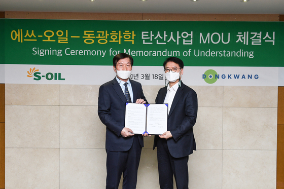 S-Oil President Ryu Yeol, right, and Park Doo-soon, vice chairman of Dongkwang Chemical, pose for a photo after signing a memorandum of understanding to cooperate on reducing carbon emission. [S-OIL]
