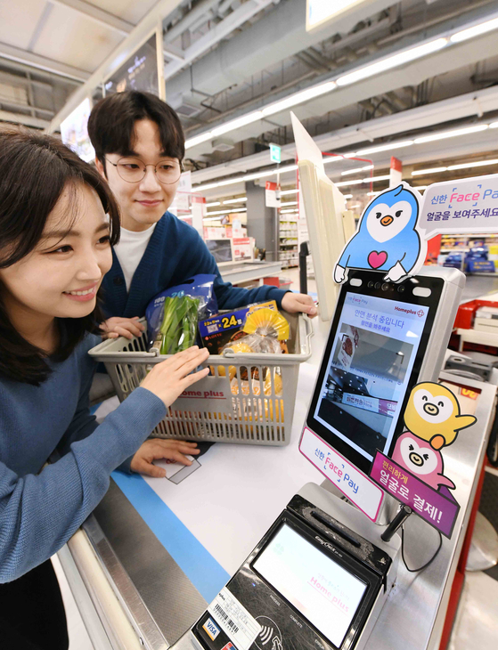 """Models demonstrate digital payment systems using facial recognition technology at a Homeplus branch in Seoul. The giant discount retail chain announced Thursday that it is first among discount supermarkets to adopt """"Shinhan Face Pay,"""" offered by Shinhan Card. [HOMEPLUS]"""