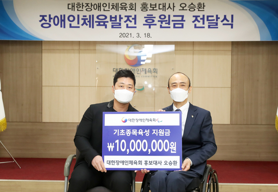Samsung Lions closer Oh Seung-hwan poses with Korea Sports Association for the Disabled Chairman Chung Jin-wan at the organizations office in Songpa District, southern Seoul.