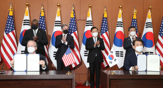Jeong Eun-bo, right, Korea's top negotiator for the defense cost-sharing negotiations, and Rob Rapson, the acting U.S. ambassador to Seoul, initial the Special Measures Agreement at a signing ceremony at the Foreign Ministry in central Seoul Thursday. U.S. Defense Secretary Lloyd Austin and Secretary of State Antony Blinken and Korea's Foreign Minister Chung Eui-yong and Defense Minister Suh Wook watch on after their two-plus-two meeting. [JOINT PRESS CORPS]
