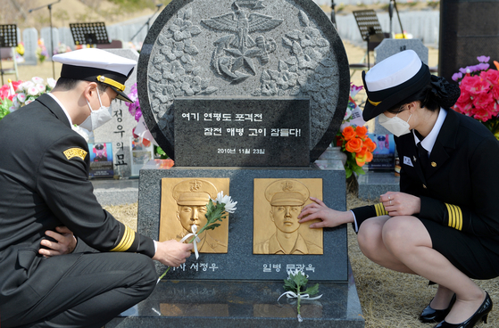At Daejeon National Cemetery on Thursday, students from Mokpo National Maritime University pay their respects to two marines killed in artillery shelling by North Korea on Yeonpyeong Island on Nov. 23, 2010. Two marines and two civilians were killed and 30 marines were injured in the shelling. [KIM SEONG-TAE]