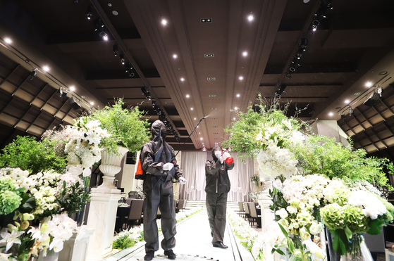 Employees sanitize a wedding hall in Suwon in August 2020. [YONHAP]
