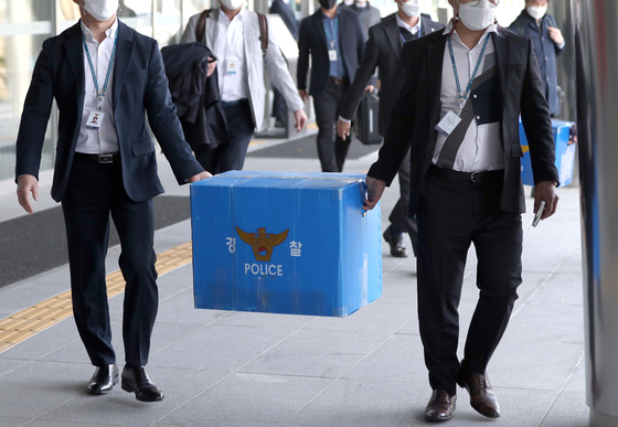 Police carrying out boxes of seized documents and files from Land and Housing Corp.'s headquarters in Jinju, South Gyeongsang on March 17 as part of its investigation on LH employees using insider information in purchasing properties. [YONHAP]