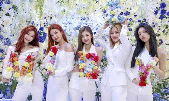"""Members of K-pop girl band ITZY hold flower-decorated letter panels, which together make the word """"MIDZY,"""" during an online concert, """"Fan Party Live,"""" on Saturday afternoon. """"MIDZY"""" is the name of ITZY's official fan club and the group's new song for the fans, which the band unveiled during the concert. [JYP ENTERTAINMENT]"""