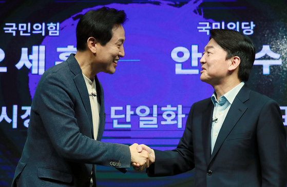 Oh Se-hoon and Ahn Cheol-soo shake hands on March 15 at a television studio in Yeongdeungpo District, Seoul after announcing their intent to support a single candidate in the Seoul mayoral by-election. [NEWS1]