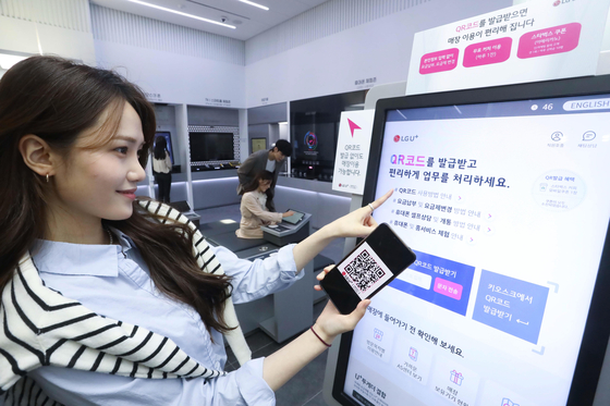 A customer uses an electronic kiosk at LG U+'s first U+ Untact store in Jongno District, central Seoul on Monday. LG U+'s first unmanned brick-and-mortar store offers a wider range of functions such as allowing new customers to open a contract with the mobile carrier and letting existing users change their phone number. [LG U+]
