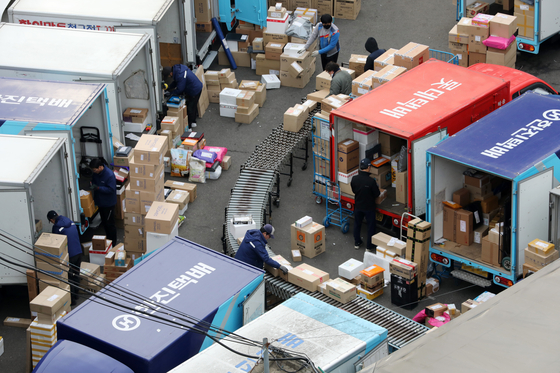 Delivery workers sort packages at a logistics facility in Seoul. [NEWS1]