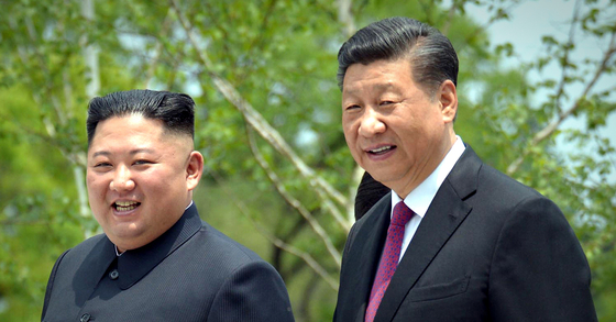 North Korean leader Kim Jong-un, left, and Chinese President Xi Jinping take a stroll at the Kumsusan State Guesthouse in Pyongyang as they hold their fifth summit in June 2019. [YONHAP]