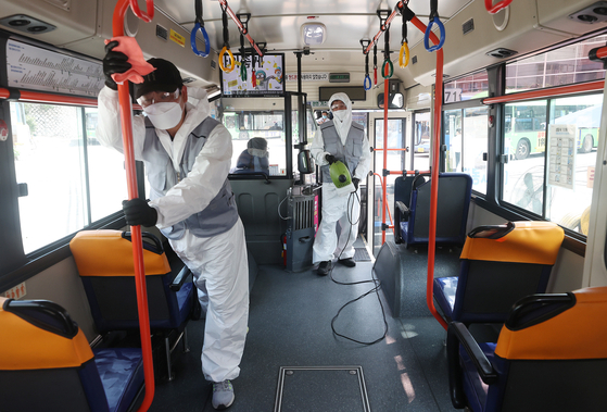 A bus is sanitized in a parking lot in Seoul in August 2020. [YONHAP]