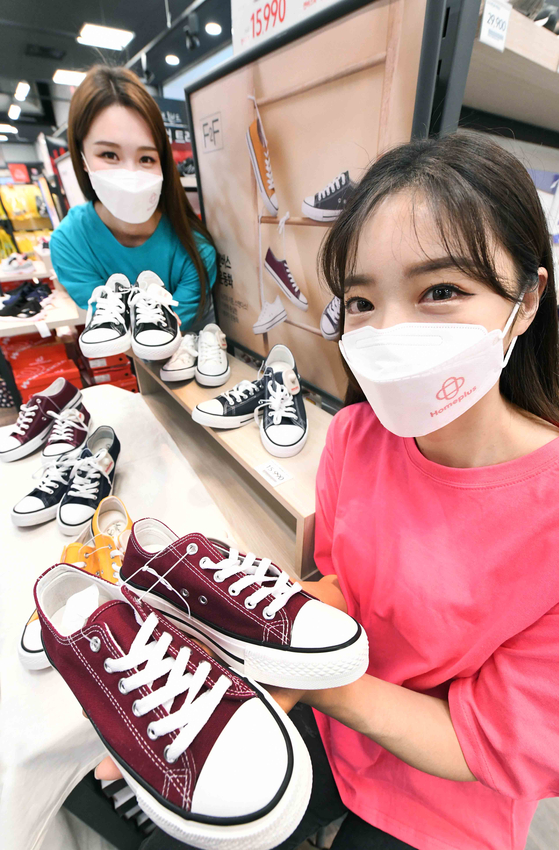 Models pose with sneakers at Homeplus' Gangseo branch in western Seoul on Tuesday. Celebrating its 24th anniversary, Homeplus is selling private brand, or PB, products such as sneakers and socks at sharply discounted prices until the end of the month. [HOMEPLUS]
