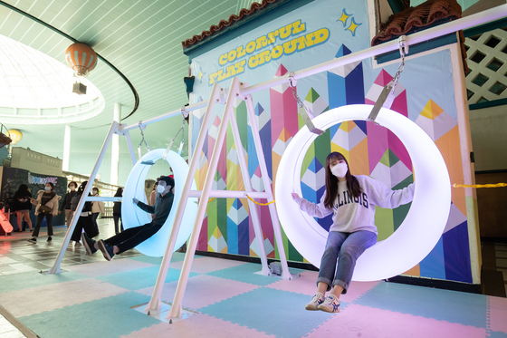 Visitors to Lotte World pose for photos at a photo zone in Songpa District, southern Seoul, on Tuesday. Lotte World is running a festival called Colorful World School until June 6, offering customers various photo zones designed as class rooms and gyms, as well as performances. [LOTTE WORLD]