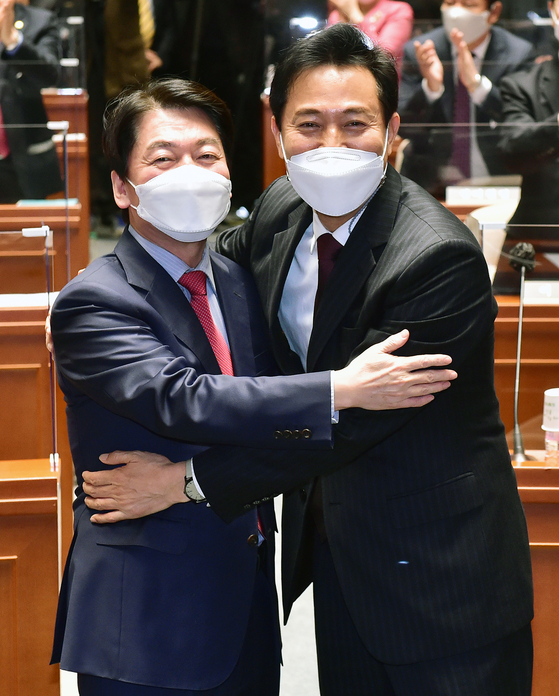 Ahn Cheol-soo, left, chairman of the People's Party, embraces Oh Se-hoon, who won the ticket of the opposition bloc to run in the Seoul mayoral by-election, at a party lawmakers' meeting in the National Assembly in Yeouido, western Seoul, on Wednesday. Ahn accepted co-chairmanship of the campaign for Oh, who beat Ahn in the preliminary opinion polls. [OH JONG-TAEK]
