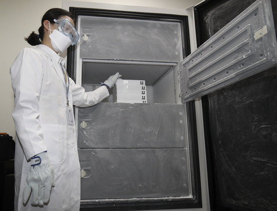 A medical staff member of a vaccination center in Ulsan stores Pfizer vaccines in a refrigerator on Wednesday. [NEWS1]