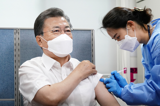 President Moon Jae-in receives his first dose of the AstraZeneca vaccine at a public health center in Jongno District, central Seoul, on Tuesday. [JOINT PRESS CORPS]