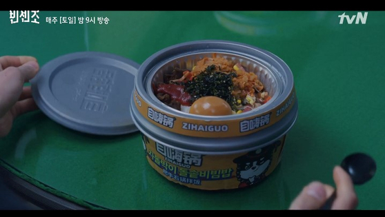 "In the tvN series ""Vincenzo"" (2021), protagonists eat a bowl of ready-to-eat 'bibimbap' — a Korean rice dish mixed with vegetables and meat — from the Chinese brand Zihaiguo. Some raised concerns that the Mandarin packaging made bibimbap seem like a Chinese dish. [SCREEN CAPTURE]"
