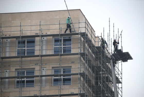 Workers work without safety harnesses at a construction site in Seoul in February. [YONHAP]