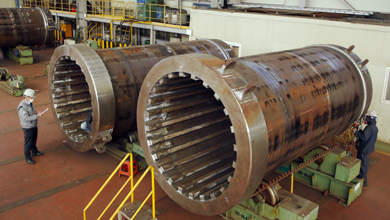 Doosan Heavy Industries & Construction workers check the production of casks to be used at Three Mile Island Nuclear Generating Station in Pennsylvania. The Korean power equipment maker said Thursday it provided five vertical concrete casks used to store spent nuclear fuel to the station under a deal with the Nuclear Assurance Corp., a U.S. provider of nuclear fuel cycle technology. [YONHAP]