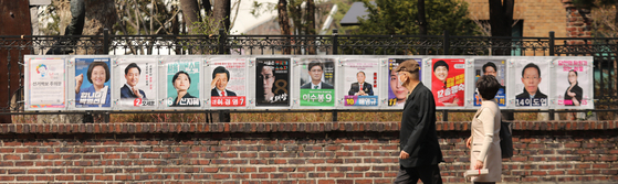 People pass by election posters for candidates running in the Seoul mayoral by-election in Jongno District, central Seoul, on Thursday as the official election campaign kicked off. [LIM HYUN-DONG]