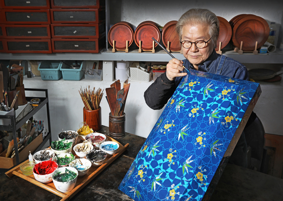 Artisan Choi Jong-kwan is adding the finishing touches to a plum and bamboo-patterned lacquer box using a fine-tip brush at his studio Chaehwa Lacquer Craft Institute in Donggyo-dong, Mapo District, western Seoul. [PARK SANG-MOON]