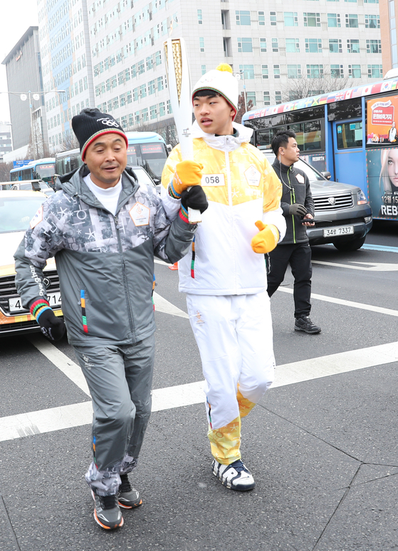 Marathoner Lee Bong-ju, left, in the torch relay for the 2018 PyeongChang Winter Olympics. [ILGAN SPORTS]