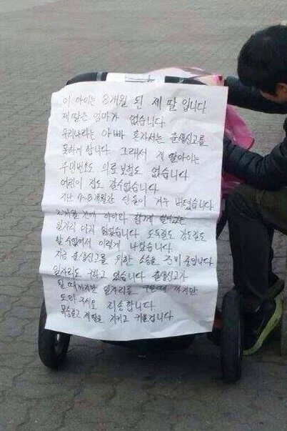 Kim Ji-hwan took his daughter Sa-rang to protest with him. The message stuck to her stroller reads, ″This is my 8-month-old daughter. She has no mother. This country does not allow a father to register a baby on his own. So my daughter does not have a social security number or health insurance.″ [KIM JI-HWAN]
