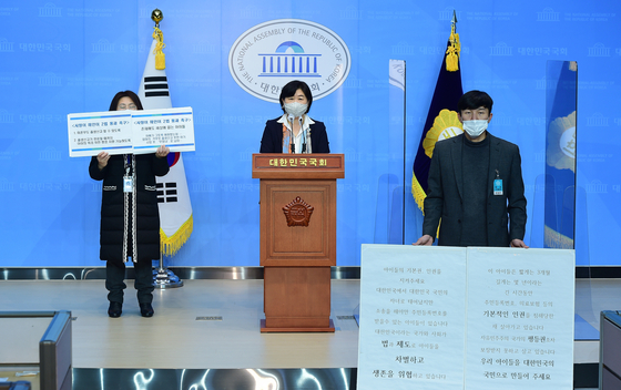 Lawmaker Seo Young-kyo, center, and Kim Ji-hwan, right, speak at a press conference to put forward an amendment to the Act on the Act on the Registration of Family Relations in January 2021 to make it easier for single fathers to register their children. [KIM JI-HWAN]