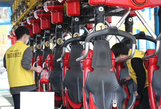 Workers disinfect rides at Children's Grand Park in Gwangjin District, eastern Seoul, on Monday, as the amusement park is scheduled to reopen on April 1. [YONHAP]