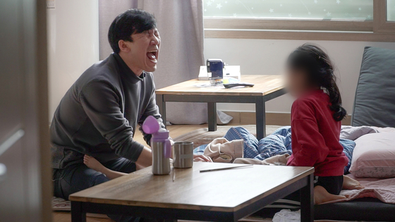 Kim Ji-hwan, left, changes a diaper of a baby of a single mother while playing with his daughter Sa-rang, right, at their home in Gyeonggi. Kim looks after the children of single parents while they are working. [JEON TAE-GYU]