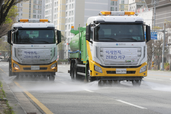 Water tank trucks spray water over the road in Gwangju on Tuesday to wash away yellow dust that blanketed the Korean Peninsula on Monday. [YONHAP]