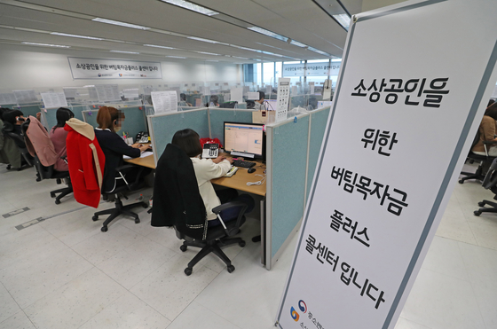 Call center employees in Daejeon handle inquires on the fourth emergency relief grants for small businesses on Tuesday. The emergency relief grants for small neighborhood shops, using funds created through this year's first supplementary budget approved last week, started to accept applicants on Tuesday. [YONHAP]