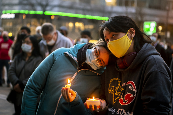 Residents in Pittsburgh console each other during a candlelight vigil on Sunday. [AP/YONHAP]