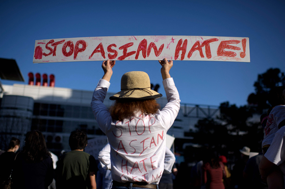 """A woman holding a sign saying """"Stop Asian Hate"""" during a rally following the fatal shooting of eight people, including six Asian women, in Atlanta last week. [AFP/YONHAP]"""