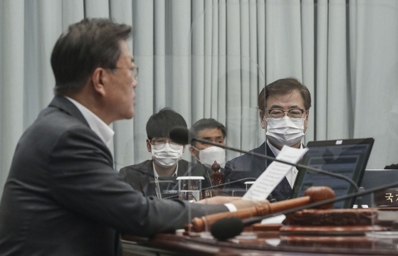 Suh Hoon, right, director of the National Security Office, listens to President Moon Jae-in at an interagency meeting at the Blue House Tuesday. Suh departed Wednesday for a trilateral meeting with his U.S. and Japanese counterparts Friday in the United States. [JOINT PRESS CORPS]