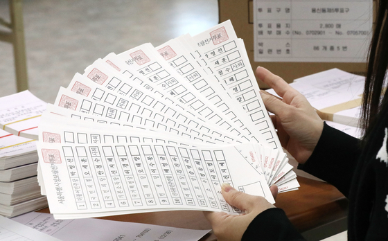 A worker examines ballots for the April 7 Seoul mayoral by-election at the Dongdaemun branch of the National Election Commission in Seoul on Wednesday. [YONHAP]