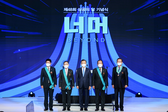 President Moon Jae-in, center, stands with the recipients of awards for advancing industries at the Korea Chamber of Commerce and Industry in central Seoul on Wednesday.[YONHAP]