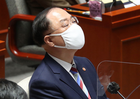 Finance Minister Hong Nam-ki on March 18 is deep in thought while listening to growing demand for fiscal input from lawmakers in the National Assembly. [AP/YONHAP]