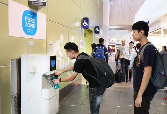 Visitors at the Kuala Lumpur International Airport use a Coway water purifier. [COWAY]