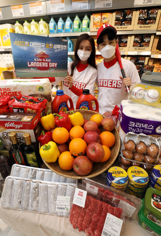 Models pose for a photo to promote the Emart Landers Day sale at an Emart branch in Seongsu-dong, eastern Seoul on Thursday. Emart will be running the Landers Day sale, named after the baseball team it owns, until April 4 to celebrate the start of the KBO season. [YONHAP]