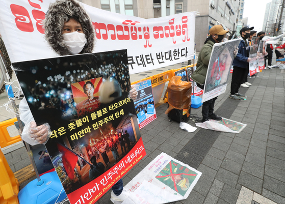 A group of protestors hold a rally against the military coup in Myanmar on Sunday in Seoul. [YONHAP]