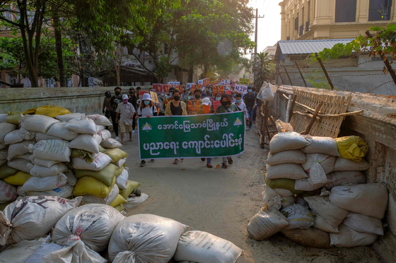 This photo received from an anonymous source via Facebook on April 1, 2021 shows protesters walking towards makeshift barricades while taking part in a demonstration against the military coup in Mandalay. [AFP]