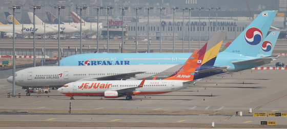 Korean Air Lines, Asiana Airlines and Jeju Air aircraft parked at Incheon International Airport on March 31. [YONHAP]