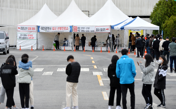 People line up to get tested for Covid-19 at the Daejeon Hanbat Sports Complex on Sunday. [KIM SUNG-TAE]