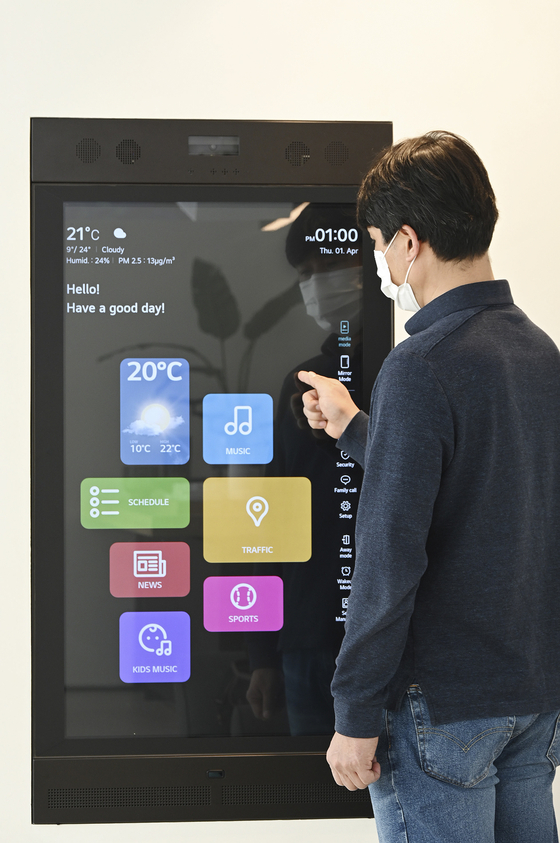 An LG Electronics employee demonstrates its Smart Mirror, which activates a KT platform that provides radio, music and other digital services. According to LG Electronics and KT on Tuesday, the two will work on developing cross-platform services. [LG ELECTRONICS, KT]