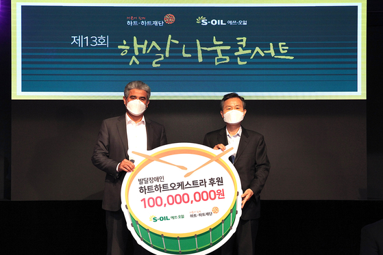 Hussain A. Al-Qahtani, S-Oil CEO, left, poses next to Oh Ji-chul, head of Heart-to-Heart Foundation, at the refinery's headquarters in Mapo, Seoul, on Tuesday. According to S-Oil, the company donated 100 million won ($89,200) to the foundation in support of an orchestra of children with developmental disabilities. The orchestra was founded in 2006. [YONHAP]