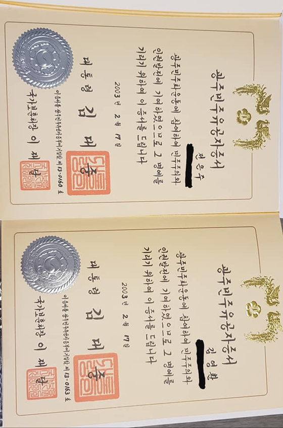 A photo of certificates, issued by former President Kim Dae-jung to recognize the merits of Kim Young-hwan, right, and his wife in the Gwangju democratization movement, is posted on Kim's Facebook. Kim said he recently returned the honors to protest the ruling party's attempt to offer more special treatments to former democracy activists and their families. [JOONGANG ILBO]