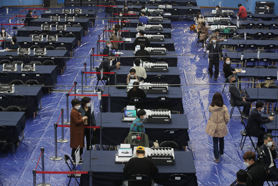 Officials from the National Election Commission have a dry run of operating electronic ballot-tallying devices at a temporary ballot-tallying center in Yangcheon District, western Seoul, on Tuesday — one day before the April 7 by-elections. [YONHAP]