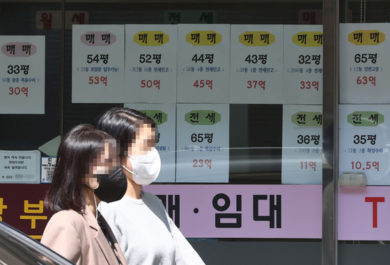 A real estate agency in Apgujeong, the most affluent neighborhood in the country, posts the price of large apartments in its window on Tuesday. According to KB Kookmin Bank, the average price of a large apartment exceeding 135 square-meter in Seoul was 2.2 billion won ($1.96 million). That's 259 million won more than a year ago. [YONHAP]