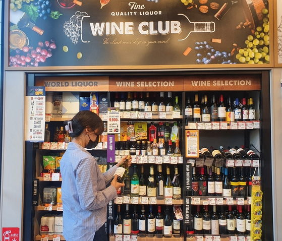 A customer looks at the wine section of an Emart24 convenience store. [EMART24]