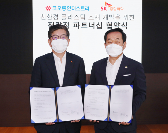 From left, SK Global Chemical CEO Na Kyung-soo and Kolon Industries CEO Jang Hee-goo sign an agreement to develop biodegradable plastic at SK's Seoul office in central Seoul, Wednesday. [SK GLOBAL CHEMICAL]